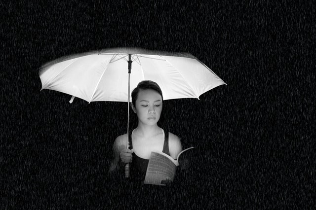 Woman holding an umbrella reading